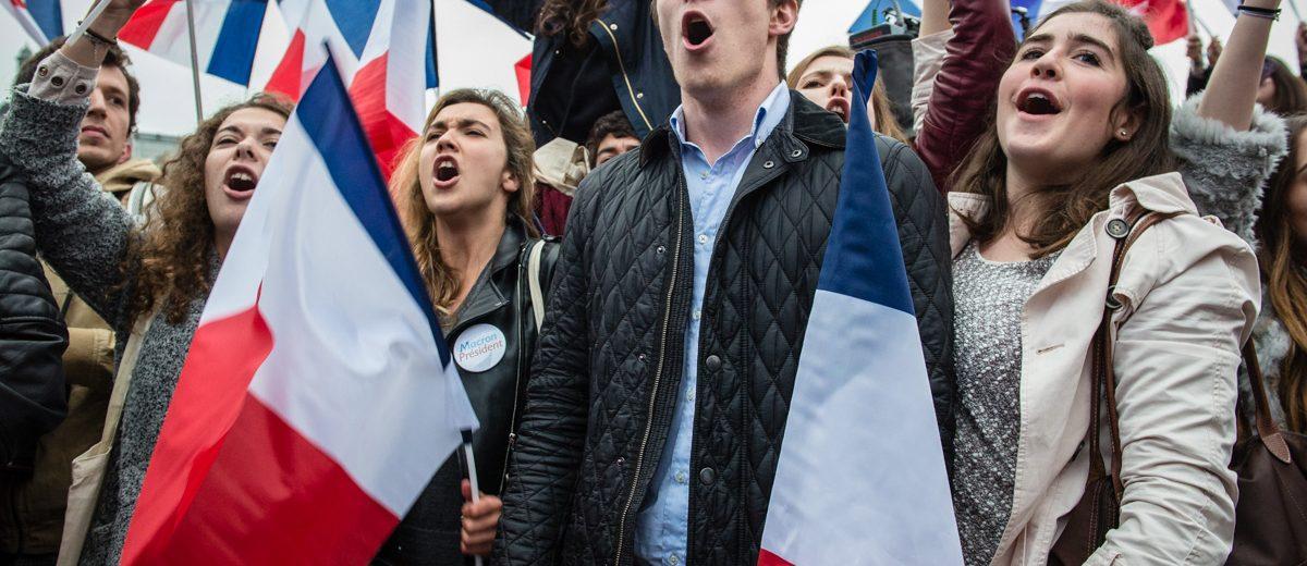 Un grupo de jóvenes simpatizantes de Emmanuel Macron cantan el himno nacional francés, La Marsellesa, al conocer los resultados finales que dieron ganador a Macron. Foto: Hugo Passarello