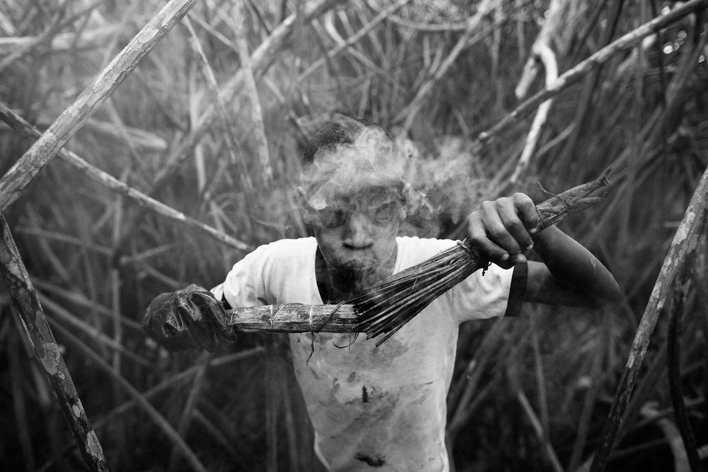 Jeffeson Muñoz ahuyenta a los mosquitos con humo. Foto: Felipe Jácome
