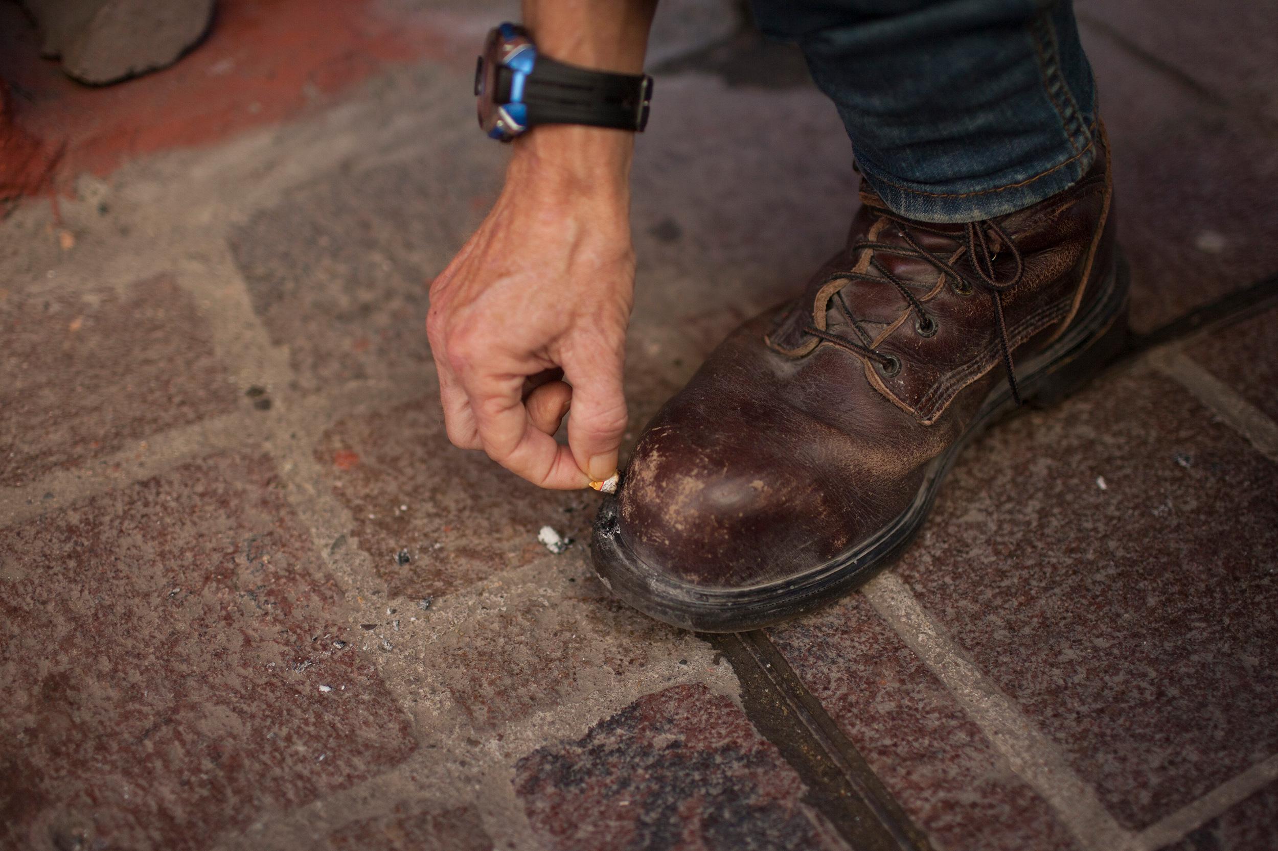 X apaga un cigarrillo en su bota. Foto: Alejandro Saldívar