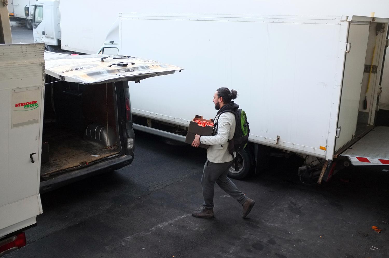 Aladdin Charni lleva dos cajas de tomates hacia la camioneta del restaurante. Es una parte de lo que logró recuperar en el mercado de Rungis. Foto: Santiago Rosero