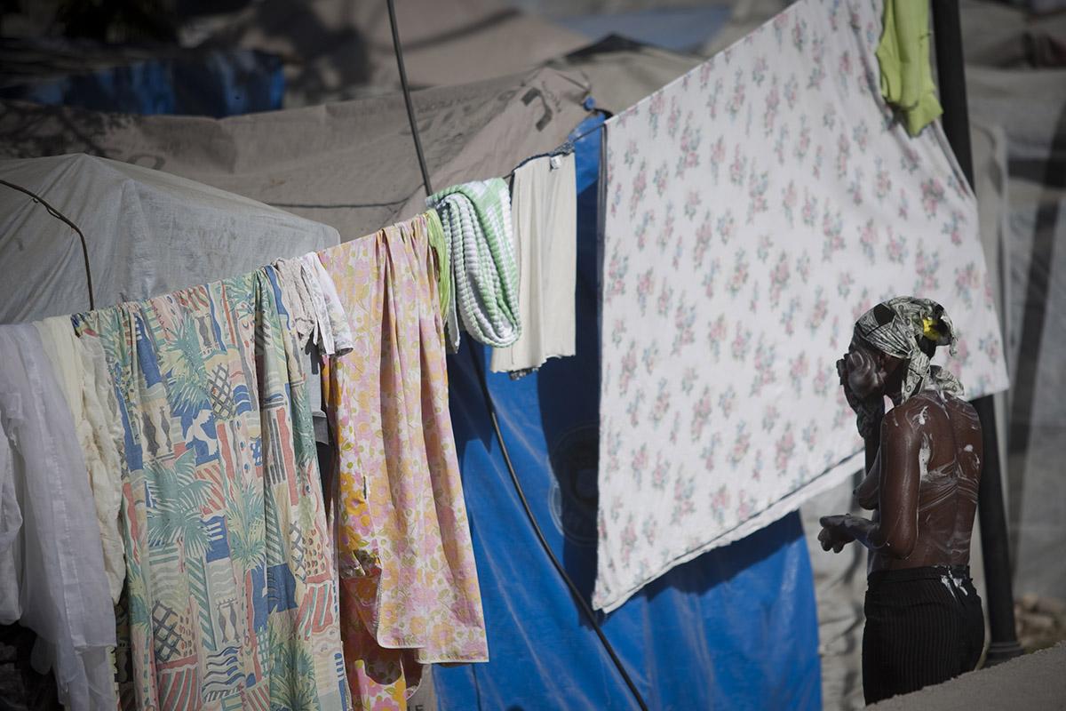 Una mujer se lava la cara en un campamento en Puerto Príncipe. Foto: Alejandro Saldívar