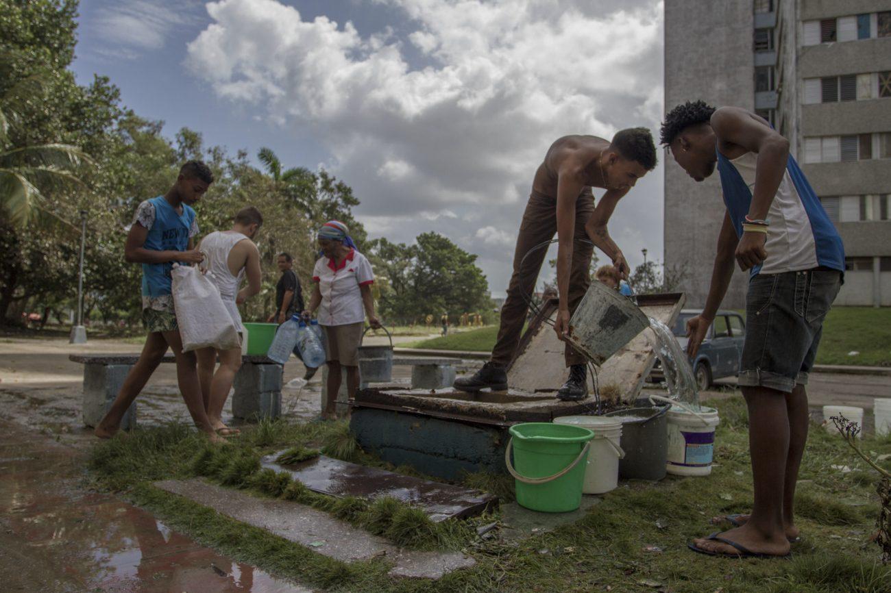 Cubanos cargan agua en un edificio, pobreza en Cuba. Foto: Dahian Cifuentes.