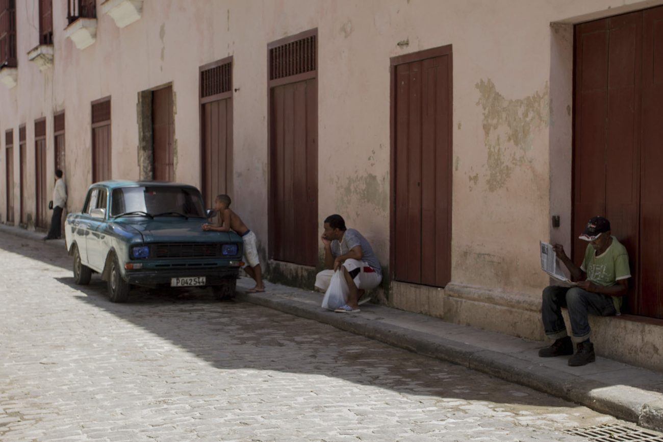 Cubanos sentados junto a un auto antiguo en La Habana. Foto: Dahian Cifuentes.